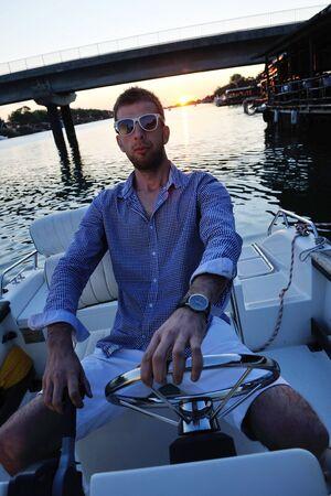 happy young man have fun at boat at sunset on summer season photo