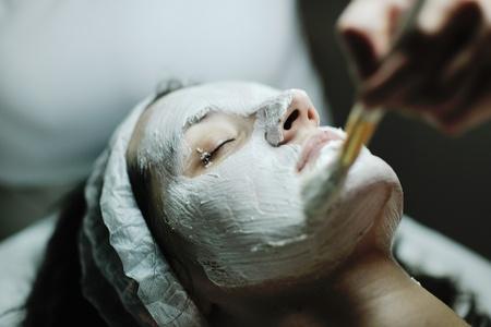 pulizia viso: Giovane bella donna riceve cosmetici maschera facciale nel salone di bellezza spa e relax