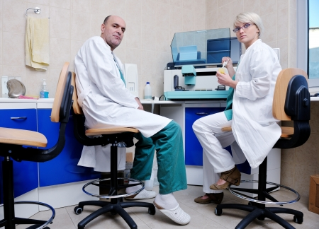 animal practice: portrait of a veterinarian and assistant in a small animal clinic at work