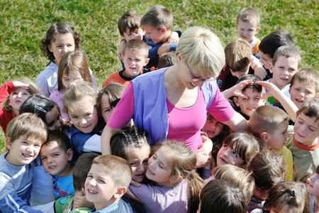 maestra preescolar: niño feliz grupo de niños se divierten y juegan en el concepto de la educación pre-escolar con la maestra de jardín de infancia