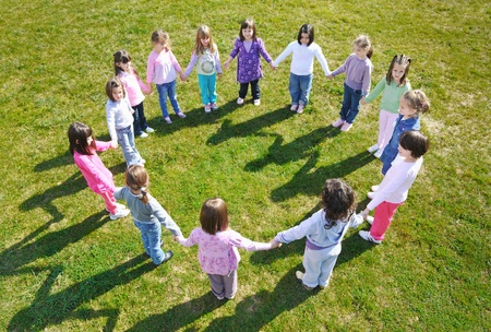 children playing together: happy child kids group have fun and play at kindergarden outdoor preschool education concept with  teacher Stock Photo