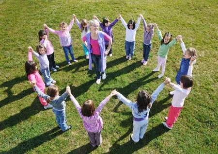 maestra preescolar: niño feliz grupo de niños se divierten y juegan al aire libre en el jardín de infantes concepto de educación preescolar con el maestro