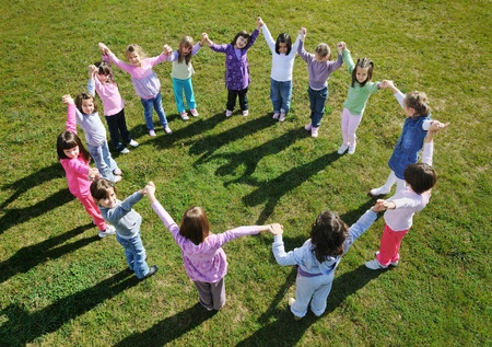 kids learning: happy child kids group have fun and play at kindergarden outdoor preschool education concept with  teacher Stock Photo
