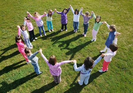 ni�as jugando: ni�o feliz grupo de ni�os se divierten y juegan en el jard�n de infancia al aire libre concepto de la educaci�n preescolar con el maestro