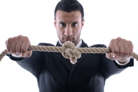Business man pulling and bond tied with rope concept isolated on white background in studio Stock Photo - 12303811