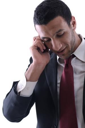 hombre arabe: Retrato de una charla de hombre de negocios con teléfono celular móvil aislado sobre fondo blanco. Foto de estudio comunicación concepto Foto de archivo