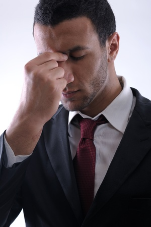 Portrait of a young business man looking depressed from work isolated over white background in studio photo