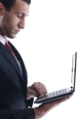 hombre arabe: Sonriente hombre de negocios espera y trabajar en comuter mini ordenador portátil aislado sobre fondo blanco en estudio Foto de archivo
