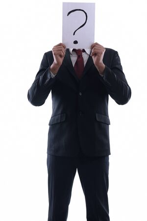 Business man holding a piece of paper over his face with a question mark on it isolated on white background in studio photo