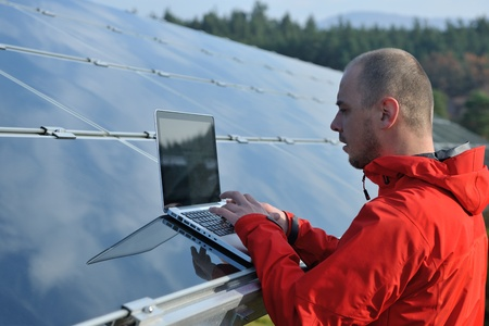 business man  engineer using laptop at solar panels plant eco energy field  in background photo