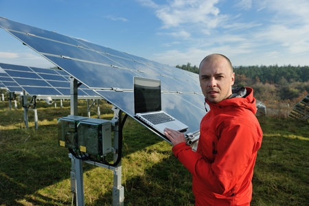 energy field: business man  engineer using laptop at solar panels plant eco energy field  in background