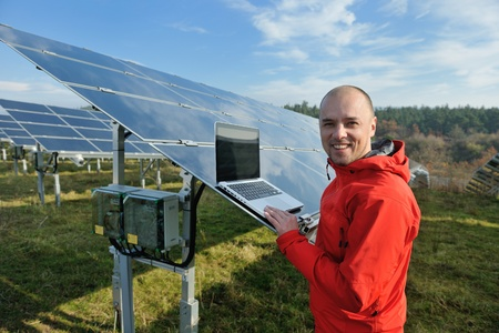 solar panel roof: business man  engineer using laptop at solar panels plant eco energy field  in background