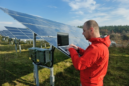 human energy: business man  engineer using laptop at solar panels plant eco energy field  in background