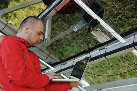 vision repair: business man  engineer using laptop at solar panels plant eco energy field  in background