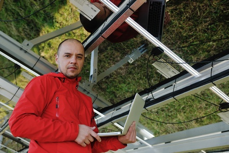 laptop repair: business man  engineer using laptop at solar panels plant eco energy field  in background