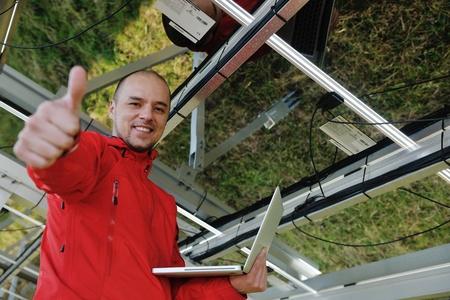 Geschäftsmann mit Laptop-Ingenieur bei Solarzellen-Anlage Öko-Energie-Feld im Hintergrund