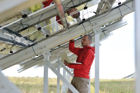 energy work: business man  engineer using laptop at solar panels plant eco energy field  in background