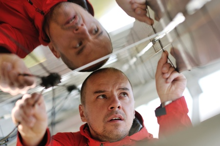 vision repair: Male engineer at work place, solar panels plant industy in background Stock Photo
