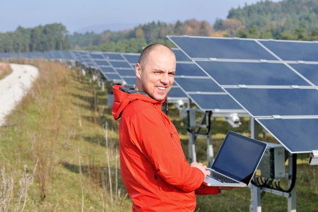 generator: business man  engineer using laptop at solar panels plant eco energy field  in background