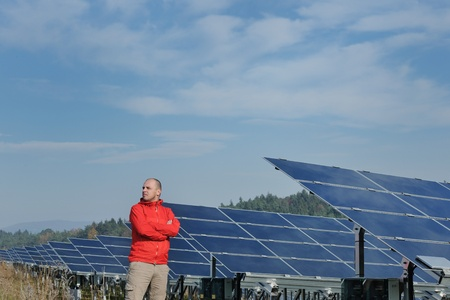 Male engineer at work place, solar panels plant industy in background photo