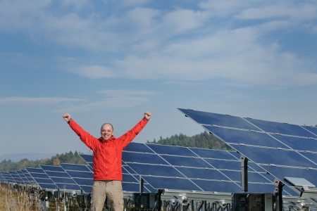 solar equipment: business man  engineer using laptop at solar panels plant eco energy field  in background