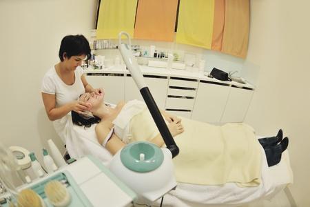 pulizia viso: Giovane donna bella ricezione di cosmetici maschera facciale in un salone di bellezza spa e relax Editoriali