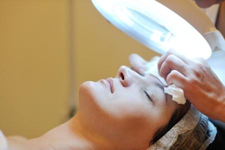 gezichtsbehandeling: Jonge mooie vrouw die cosmetische gezichtsmasker in spa beauty salon en ontspannen Stockfoto