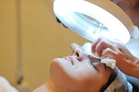 facial treatment: Young beautiful woman receiving cosmetic facial mask in spa beauty salon and relax