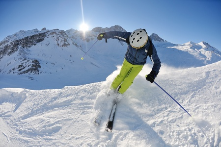 skier skiing downhill on fresh powder snow  with sun and mountains in background photo