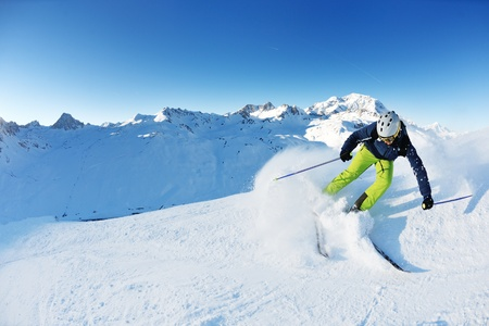 fresh snow: skier skiing downhill on fresh powder snow  with sun and mountains in background