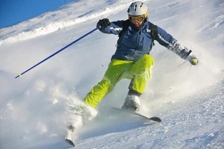 skiër skiën afdaling op verse poeder sneeuw met zon en bergen in de achtergrond Stockfoto