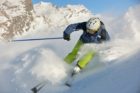 skier skiing downhill on fresh powder snow  with sun and mountains in background Stock Photo - 12304094