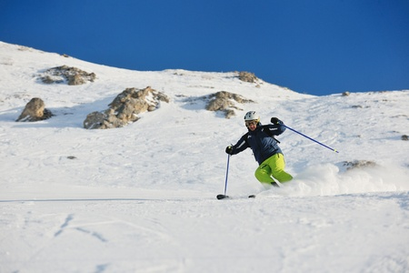 powder snow: skier skiing downhill on fresh powder snow  with sun and mountains in background