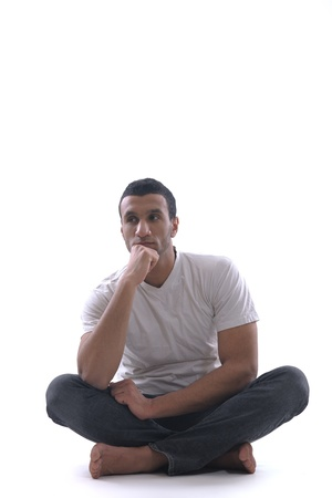portrait of relaxed young man dressed in white shirt and jeans isolated over white background in studio photo