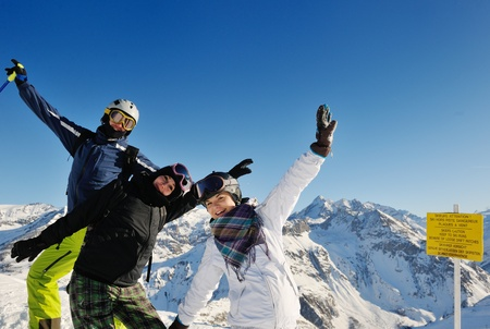 happy people group have fun on ski snow at winter season on mountain with blue sky and fresh air photo