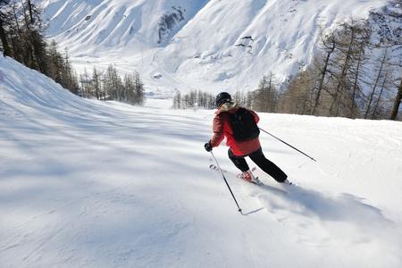 skiër skiën afdaling op verse poeder sneeuw met zon en bergen in de achtergrond