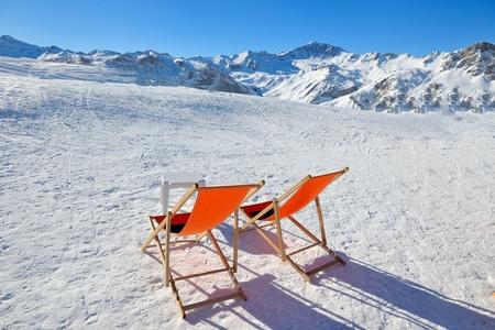 日当たりの良い冬のシーズンでの山の範囲の上に椅子リラックスの概念を表す背景の青い空の日