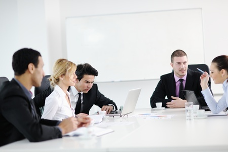 Group of young business people sitting in board room during meeting and discussing with paperwork photo