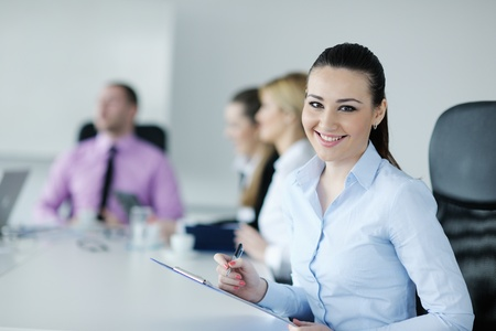 Successful business woman standing with her staff in background at modern bright office Stock Photo - 12565226