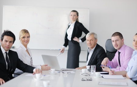 Group of young business people sitting in board room during meeting and discussing with paperwork Stock Photo - 12565355