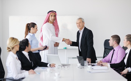Business meeting - Handsome young Arabic  man presenting his ideas to colleagues and listening for ideas for success investments at bright modern office room Stock Photo - 12565323