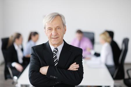 mujeres mayores: la gente de negocios equipo durante una reunión en un entorno de oficina ligero y moderno.