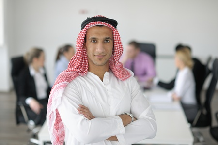 Business meeting - Handsome young Arabic  man presenting his ideas to colleagues and listening for ideas for success investments at bright modern office room Stock Photo - 12565294