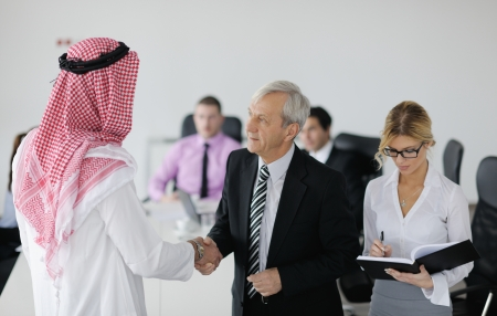 arab man: Business meeting - Handsome young Arabic  man presenting his ideas to colleagues and listening for ideas for success investments at bright modern office room