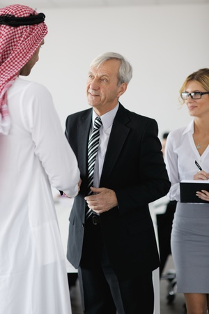 Business meeting - Handsome young Arabic  man presenting his ideas to colleagues and listening for ideas for success investments at bright modern office room Stock Photo - 12565376