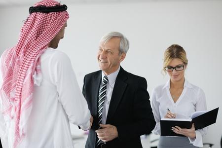 hombre arabe: Reunión de negocios - guapo hombre árabe joven presentar sus ideas a los colegas y escuchar ideas para inversiones exitosas en habitación luminosa oficina moderna