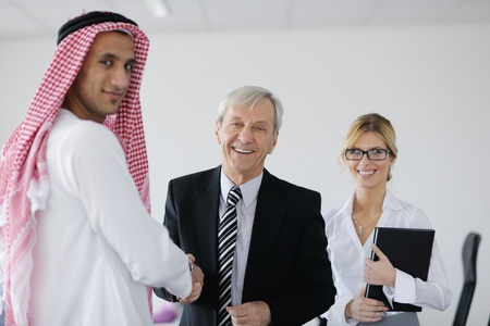 arabic woman: Business meeting - Handsome young Arabic  man presenting his ideas to colleagues and listening for ideas for success investments at bright modern office room