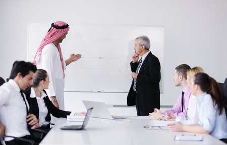 arab people: Business meeting - Handsome young Arabic  man presenting his ideas to colleagues and listening for ideas for success investments at bright modern office room