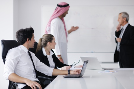 Business meeting - Handsome young Arabic  man presenting his ideas to colleagues and listening for ideas for success investments at bright modern office room photo