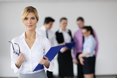office staff: Successful business woman standing with her staff in background at modern bright office